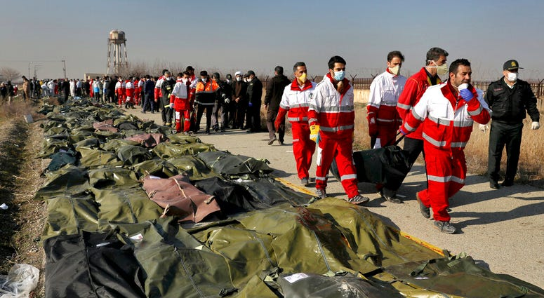 Rescue workers carry the body of a victim of a Ukrainian plane crash in Shahedshahr, southwest of the capital Tehran, Iran