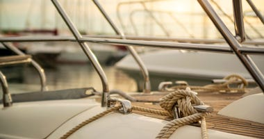 White mooring rope tied around steel anchor on boat