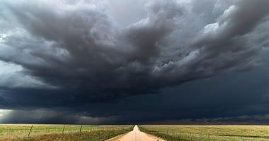 Dark storm clouds over a dirt road