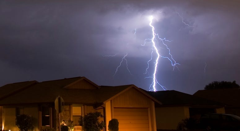 Lightning strikes in the night near family houses