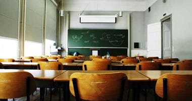 A large, empty classroom with wooden chairs.