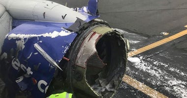 The engine on a Southwest Airlines plane is inspected as it sits on the runway at the Philadelphia International Airport after it made an emergency landing in Philadelphia