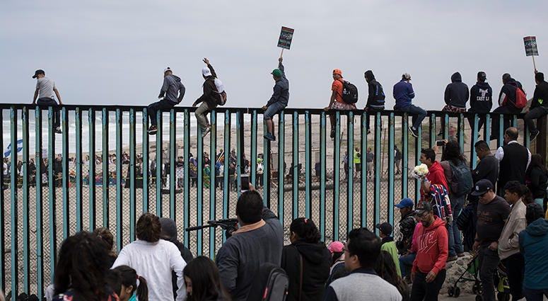 Central American migrants traveling with a caravan gather at the border wall, some sitting on top of it, look toward the U.S. from Mexico during a gathering of migrants living on both sides of the border, on the beach where the border wall ends in the oce
