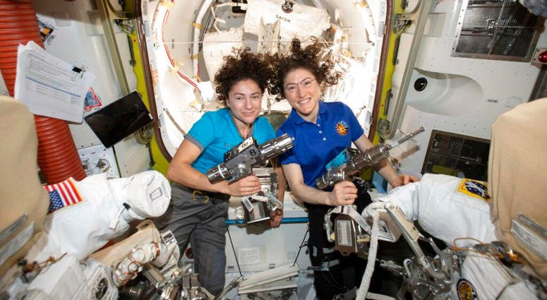 U.S. astronauts Jessica Meir, left, and Christina Koch pose for a photo in the International Space Station