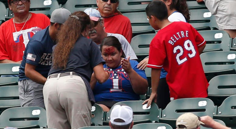 Rangers fans is attended to after being hit in the head with a ball