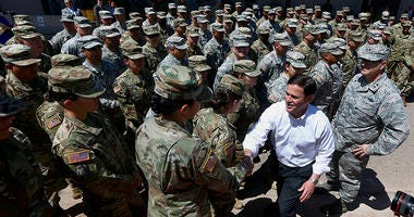 Arizona's Republican Gov. Doug Ducey, front right, meets with Arizona National Guard soldiers prior to their deployment to the Mexico border at the Papago Park Military Reservation on Monday, April 9, 2018, in Phoenix. Ducey told the group of soldiers pre