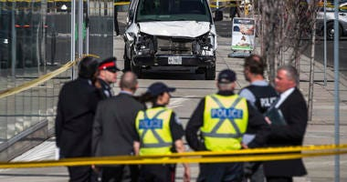 Police are seen near a damaged van after a van mounted a sidewalk crashing into pedestrians in Toronto on Monday, April 23, 2018. The van apparently jumped a curb Monday in a busy intersection in Toronto and struck the pedestrians and fled the scene befor