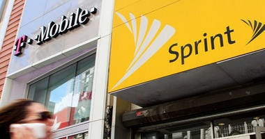 FILE- In this April 27, 2010 file photo, a woman using a cell phone walks past T-Mobile and Sprint stores in New York. T-Mobile and Sprint are trying again to combine in a deal that would reshape the U.S. wireless landscape, the companies announced Sunday