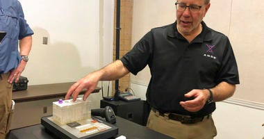 Stephen Meer, chief information officer from ANDE, demonstrates in Chico, Calif., his company's Rapid DNA analysis system.