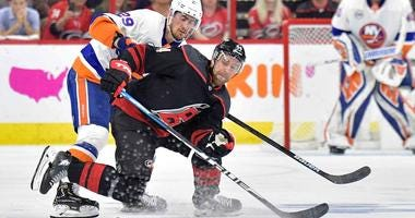Brock Nelson of the New York Islanders and Calvin de Haan of the Carolina Hurricanes battle for a loose puck during Game 3 of their NHL playoff series.