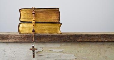 Rosary beads and books of Catholic Church liturgy