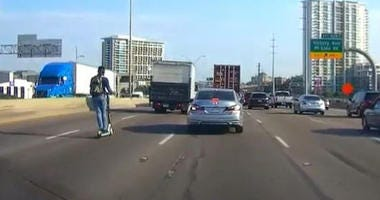 Man Riding Electric Scooter On Interstate