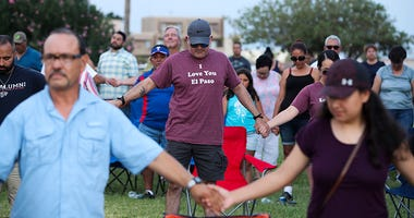 People take part in a prayer and vigil at Ponder Park in El Paso, Texas,