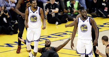 Golden State Warriors forward Kevin Durant (35) reacts to a call while standing over Cleveland Cavaliers forward LeBron James during the second half of Game 1 of basketball's NBA Finals in Oakland, Calif., Thursday, May 31, 2018
