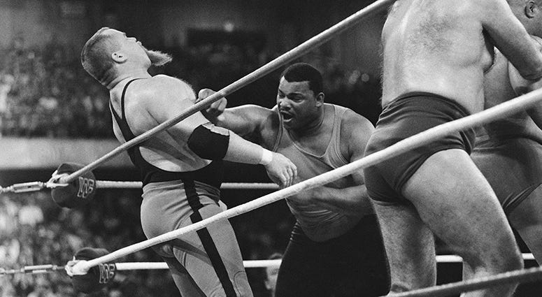 """File-This April 7, 1986, file photo shows Chicago Bears' William Perry, right, landing a punch on pro wrestler Jim """"The Anvil"""" Neidhart during the """"Over-The-Top-Rope"""" battle royal at Wrestlemania 2"""