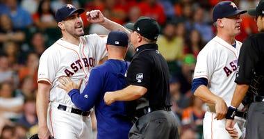 Houston Astros starting pitcher Justin Verlander, left, yells at home plate umpire Pat Hoberg