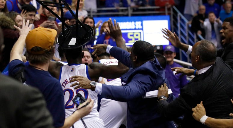 A fight between players spills into the crowd during the second half of an NCAA college basketball game between Kansas and Kansas State in Lawrence, Kan.,