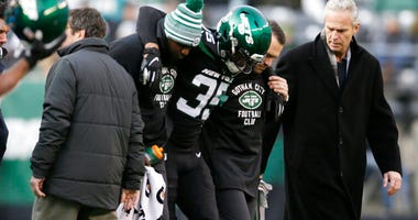 New York Jets cornerback Kyron Brown (35) is helped off the field after being injured
