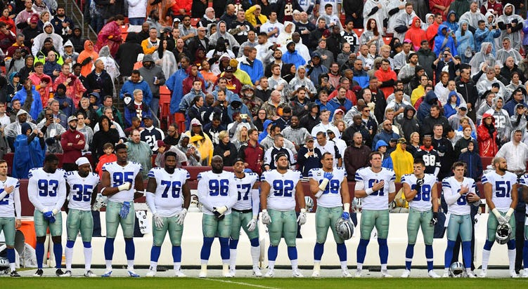 Dallas Cowboys players stand for the national anthem against the Washington Redskins before the game at FedEx Field.
