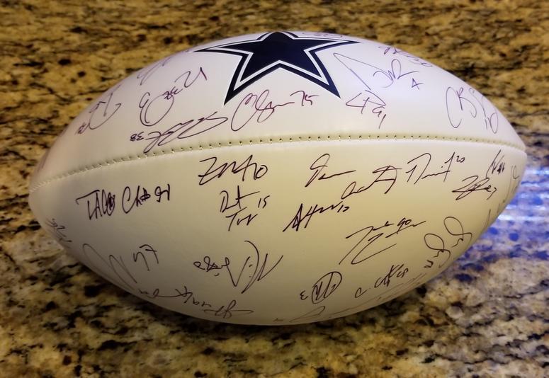 Cowboys team signed football.