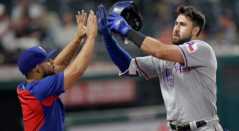 Texas Rangers' Rougned Odor, left congratulates Joey Gallo after Gallo hit a solo home run in the 12th inning of a baseball game against the Cleveland Indians, Tuesday, May 1, 2018, in Cleveland. The Rangers won 8-6