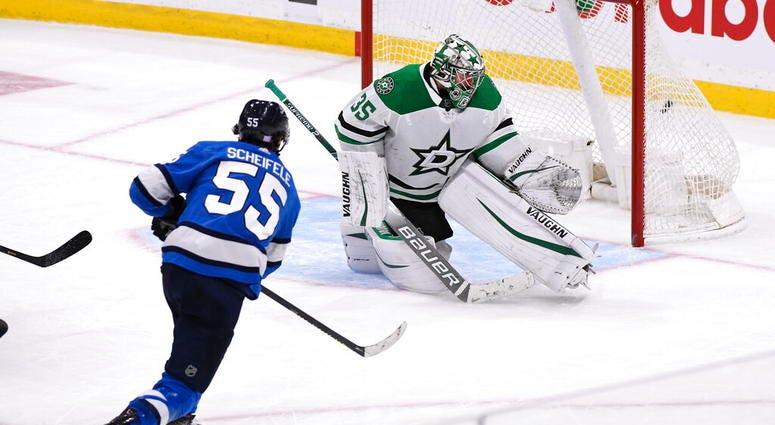 Winnipeg Jets' Mark Scheifele (55) scores the winning goal in overtime against Dallas Stars goaltender Anton Khudobin