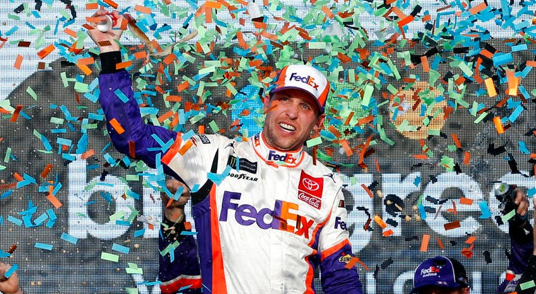 Denny Hamlin celebrates in Victory Lane after winning the NASCAR Cup Series auto race