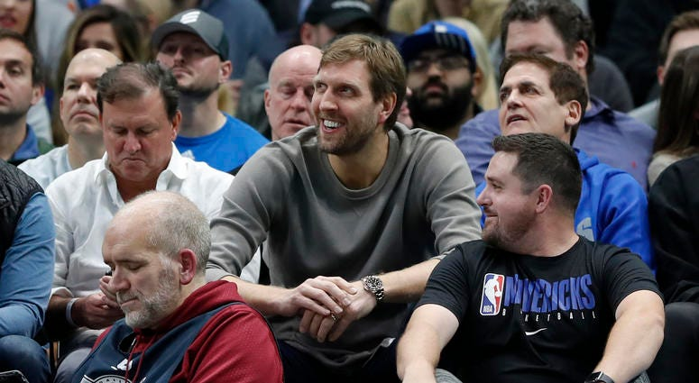 Former player Dirk Nowitzki, center, and team owner Mark Cuban, right, watch play between the Cleveland Cavaliers and Dallas Mavericks in the second half of an NBA basketball game in Dallas, Friday, Nov. 22, 2019.