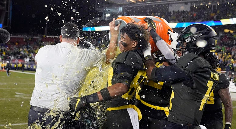 Oregon players douse coach Mario Cristobal near the end of the team's 37-15 win over Utah in an NCAA college football game for the Pac-12 Conference championship in Santa Clara, Calif., Friday, Dec. 6, 2018
