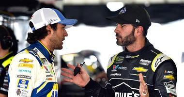 Jimmie Johnson, right, talks to Chase Elliott in the garage area