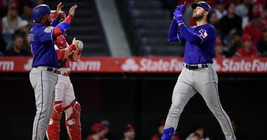 Texas Rangers' Joey Gallo, right, gestures as he scores after hitting a three-run home run as Elvis Andrus, left, waits to congratulate him and Los Angeles Angels catcher Jonathan Lucroy stands at the plate during the first inning of a baseball game Thurs