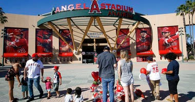 Mourners stand at a memorial to give their condolences for Los Angeles Angels pitcher Tyler Skaggs at Angel Stadium in Anaheim, Calif.