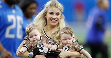 Kelly Stafford, wife of Detroit Lions quarterback Matthew Stafford, carries their twin daughters on the field during a game in 2017.