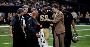 New Orleans Saints offensive guard Larry Warford (67) is helped off the field by trainers after suffering a concussion