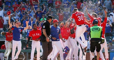 Texas Rangers right fielder Nomar Mazara (30) is greeted at home plate by teammates after hitting a walk off solo homerun in the 10th inning against the Detroit Tigers at Globe Life Park in Arlington