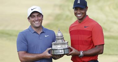 Francesco Molinari of Italy (L) celebrates with the championship trophy with Tiger Woods of the United States