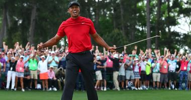 Tiger Woods celebrates after making a putt on the 18th green to win The Masters golf tournament