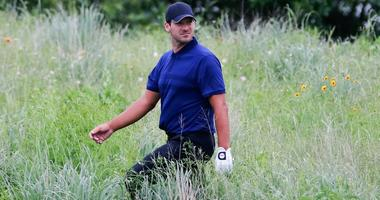 Tony Romo looks for his ball in the native grass on the 15th hole during the first round of the AT&T Byron Nelson