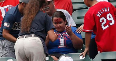 Texas Rangers fans is attended to after being hit in the head with a ball