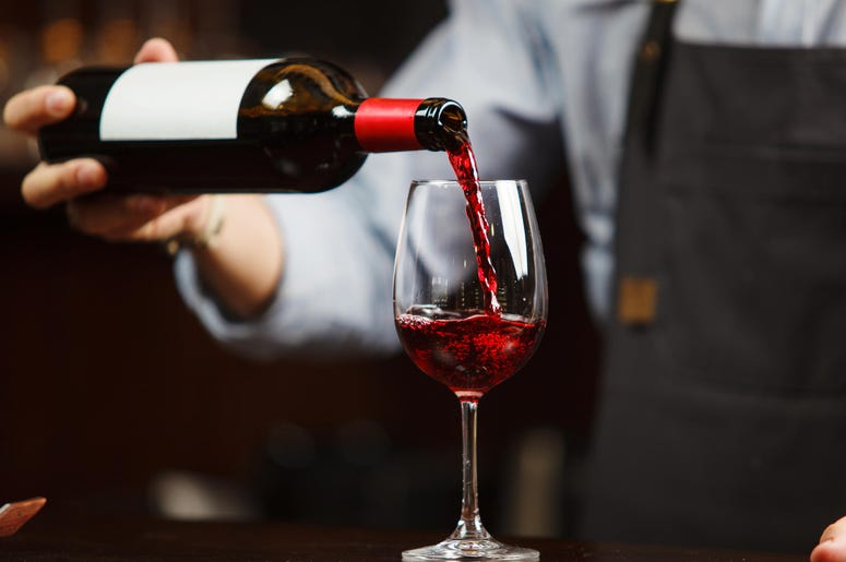 Waiter pouring red wine into wineglass.