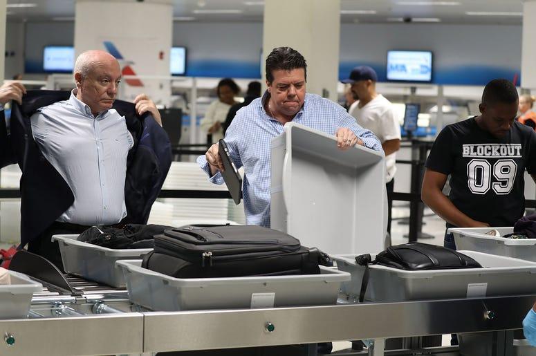 2 men at a TSA checkpoint at an airport