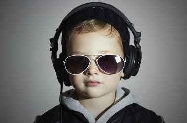 Little boy listens to music through headphones