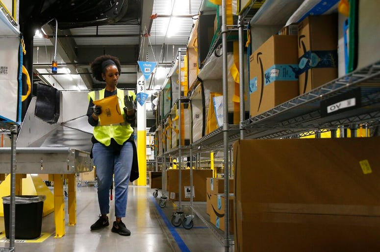In this Dec. 17, 2019, file photo, Tahsha Sydnor stows packages into special containers after Amazon robots deliver separated packages by zip code at an Amazon warehouse facility in Goodyear, Ariz. On Monday, March 16, 2020, Amazon said that it needs to h