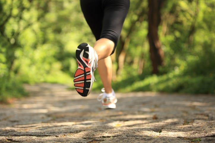 Runner athlete legs running on forest trail