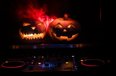Halloween pumpkin on a dj table with headphones on dark background with copy space. Happy Halloween festival decorations and music.