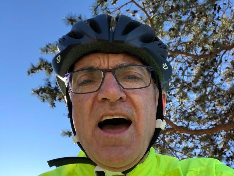 John riding a bike and smiling
