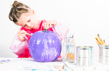 Girl painting pumpkin purple
