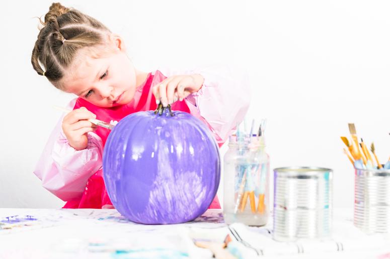 Girl painting pumpkin purple