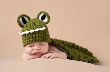 Baby sleeping in alligator crocheted blanket