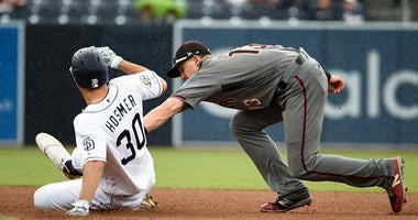 Eric Hosmer #30 of the San Diego Padres is tagged out at second base by Nick Ahmed #13 of the Arizona Diamondbacks during the fourth inning of a baseball game at Petco Park May 22, 2019 in San Diego, California. (Photo by Denis Poroy/Getty Images)